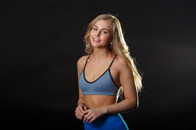 Een jonge blonde tiener in fithess kleding