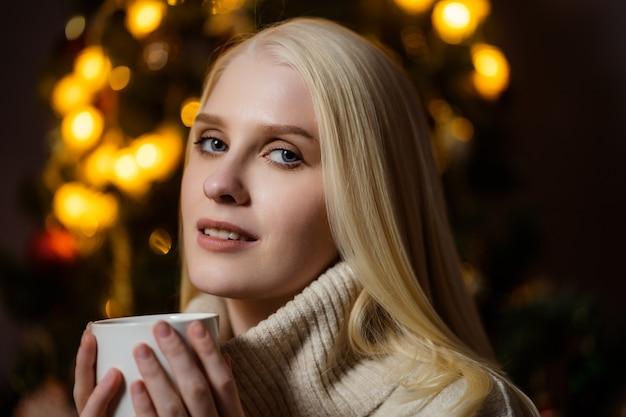 Een jonge blonde vrouw drinkt geurige cacao thuis in de buurt van een kerstboom.