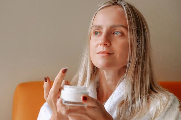 Een jonge blonde vrouw houdt een gezichtscrème.