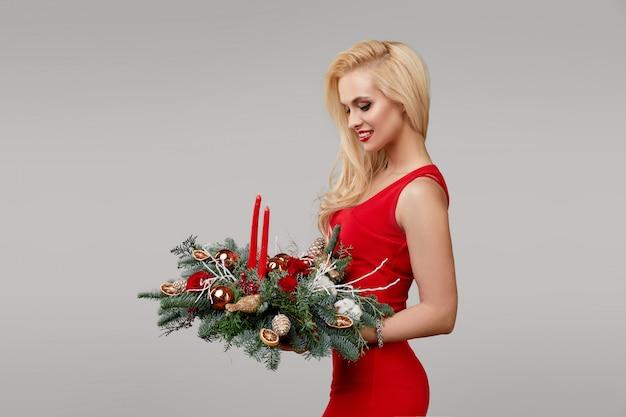 Een jonge blonde vrouw in een rode jurk heeft een kerstkrans in haar handen. feestelijk boeket bloemen en kerstboom takken op een grijze neutrale achtergrond