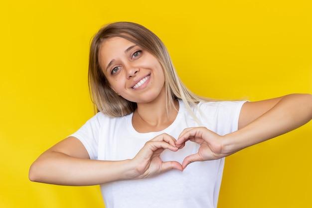 Een jonge blonde vrouw in een witte t-shirt die een hartvorm vormt met handen op een gele achtergrondkleur