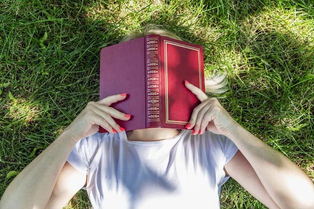 Een jonge blonde vrouw ligt in een park op het gras met haar gezicht bedekt met een boek.