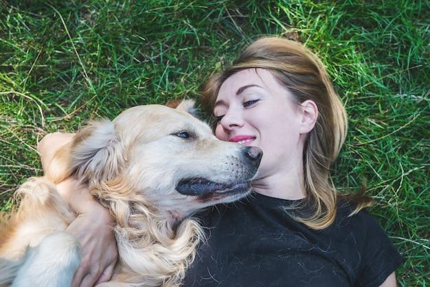 Een jonge blonde vrouw ligt op het gras met haar hond. hondenras retriever met een meisje in het park.