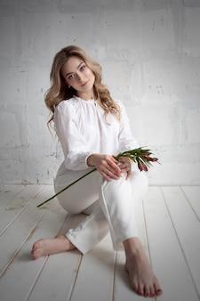 Een jonge blonde vrouw met een bloem in haar handen zit op de vloer. mode studio portret