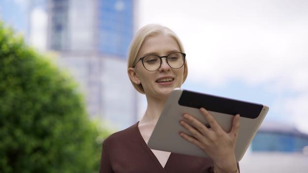 Een jonge blonde vrouw met een bril scrolt met belangstelling op straat over de tablet. verslaving aan telefoons en andere gadgets.