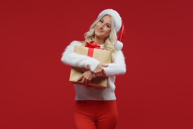 Een jonge blonde vrouw met een kerstmuts en een witte donzige trui houdt een geschenkdoos met een rode strik in haar hand. viert kerstmis