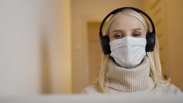Een jonge blonde vrouw met een koptelefoon en een medisch masker communiceert via een videogesprek via een laptop. werken op afstand tijdens een pandemie. 4k uhd