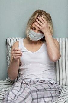 Een jonge blonde vrouw met een medisch masker ligt op het bed en is ziek. ernstige allergieën en de pandemie van het coronavirus. verticaal.