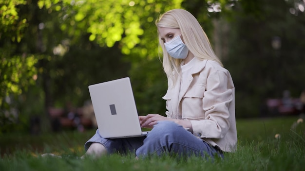 Een jonge blonde vrouw met een medisch masker typt tekst op een laptoptoetsenbord. werken op afstand in de frisse lucht. 4k uhd