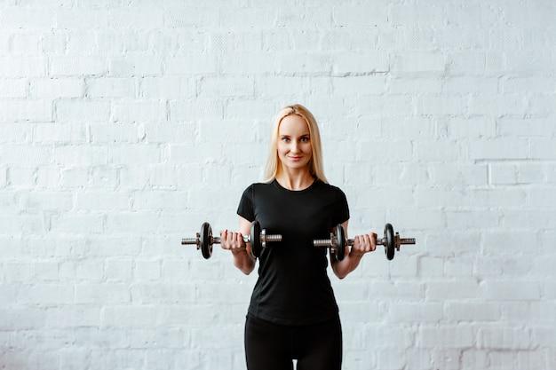 Een jonge blonde vrouw met een zwart t-shirt poseert tegen een bakstenen en witte muur en houdt vouwende halters in de hand.