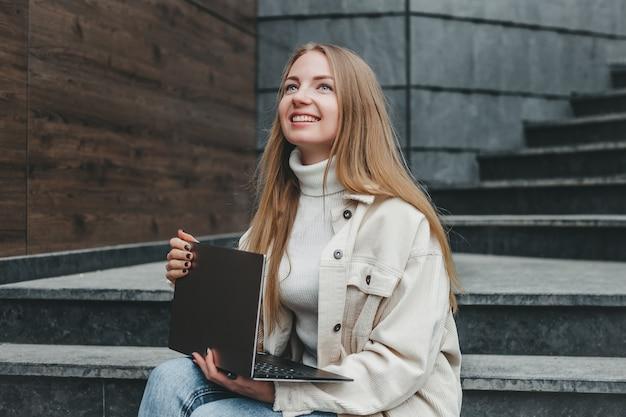 Een jonge blonde vrouw zit met een laptop op de trap lacht, droomt en kijkt op. online werken op afstand