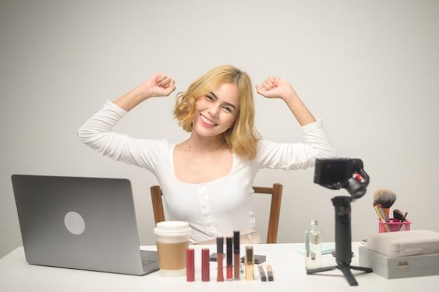 Een jonge blonde vrouwelijke ondernemer die met laptop werkt, presenteert cosmetische producten tijdens online livestream over witte achtergrondstudio, die online en beauty blogger-concept verkoopt Premium Foto