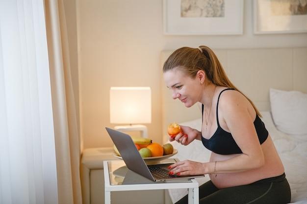 Een jonge blonde zwangere vrouw zit op het bed en eet fruit terwijl ze naar haar laptop kijkt. hoge kwaliteit foto