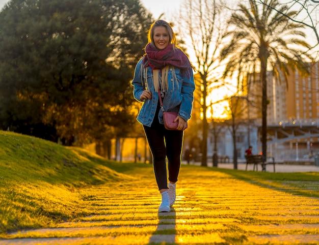 Een jonge blondine met een jasje loopt door de straten van bilbao