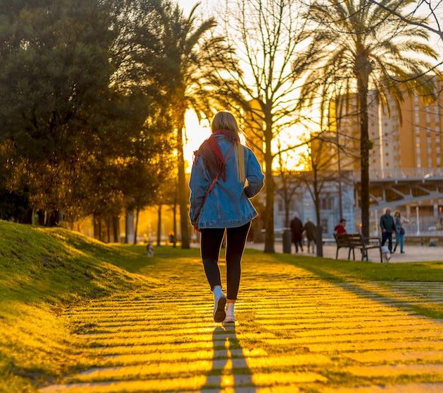 Een jonge blondine op haar rug met een jasje loopt door de straten van bilbao