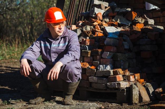 Een jonge bouwvakker in een oranje helm en beschermende bril zit op een pallet met een baksteen.