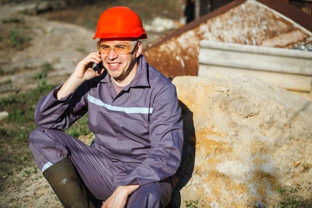 Een jonge bouwvakker in een oranje helm en beschermende bril zit op een stapel zand.