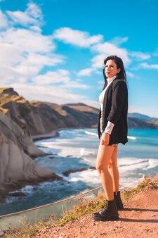 Een jonge brunette geniet van een zomermiddag aan de kust van baskenland, zumaia. gipuzkoa