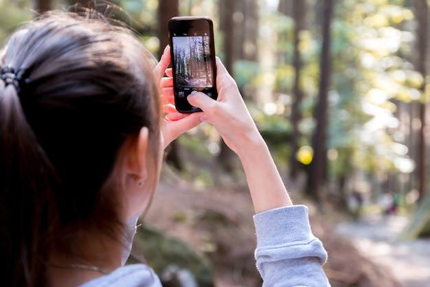 Een jonge brunette in een bos neemt een foto op hun smartphone