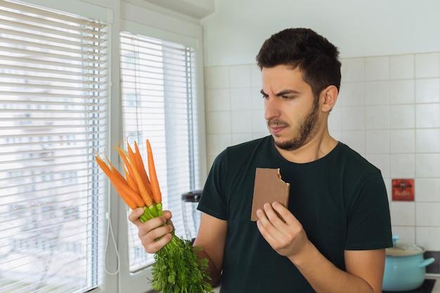 Een jonge brunette man kijkt naar een wortel met minachting en walging. een persoon leidt geen gezonde levensstijl, hij wil snoep eten en geen gezond voedsel.