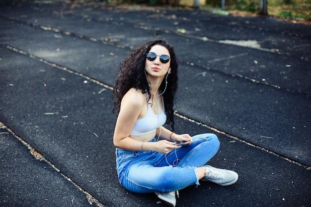 Een jonge brunette met een bril met lang krullend haar zit op de grond in de straat in een witte top en een spijkerbroek met een tablet in haar handen en een koptelefoon in haar oren. geniet van het leven. levensstijl.