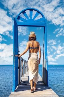 Een jonge brunette passeert een blauwe deur in de caribische zee op roatán island. honduras