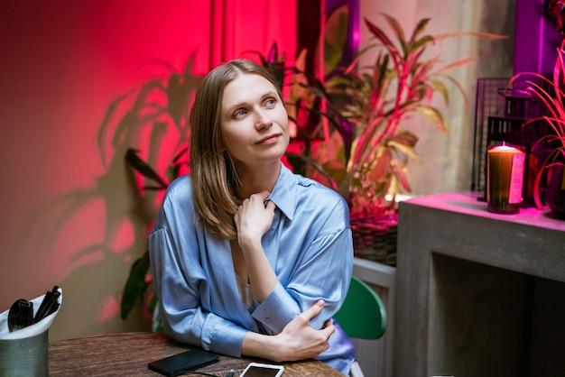 Een jonge brunette vrouw in een blauw shirt zit in een gezellige kamer en droomt.