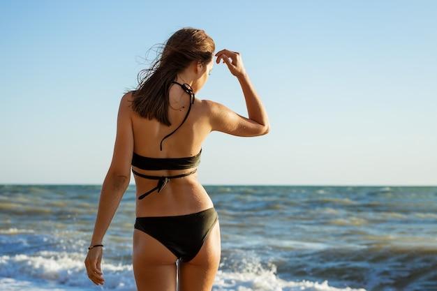 Een jonge brunette vrouw in een gespleten zwarte zwembroek staat aan de kust.