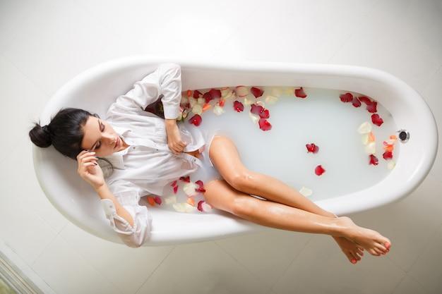 Een jonge brunette vrouw neemt een melkbad.