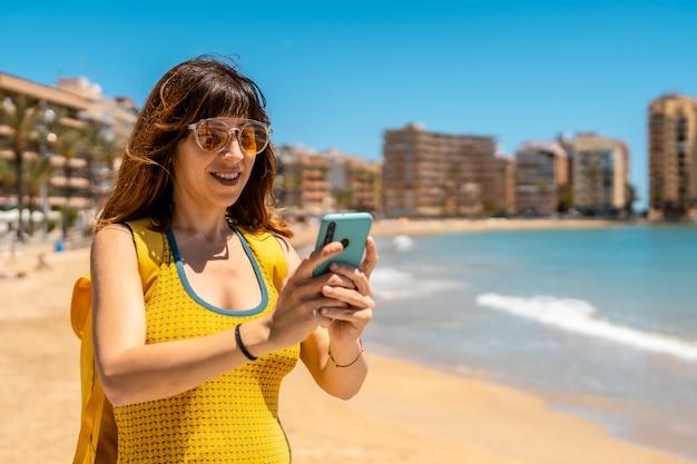 Een jonge buitenlandse toerist met de telefoon in playa del cura in de kustplaats torrevieja, alicante, valenciaanse gemeenschap