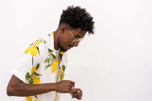 Een jonge cubaanse man in een gebloemd hemd en een bril die lacht en danst op een witte achtergrond, kopieer en plak de ruimte
