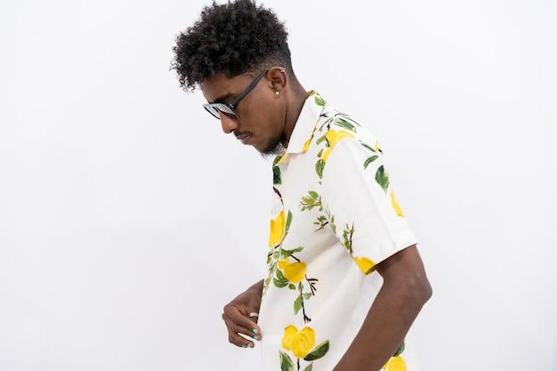 Een jonge cubaanse man in een gebloemd hemd en een zonnebril die danst op een witte achtergrond