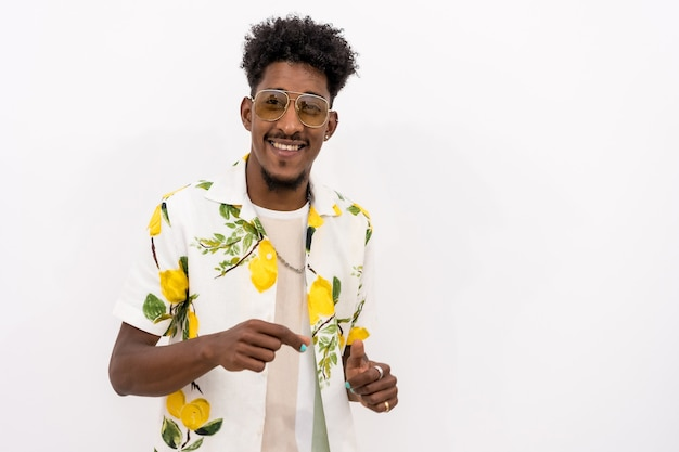 Een jonge cubaanse man met een bloemenoverhemd en een bril die lacht op een witte achtergrond, kopieer en plak de ruimte