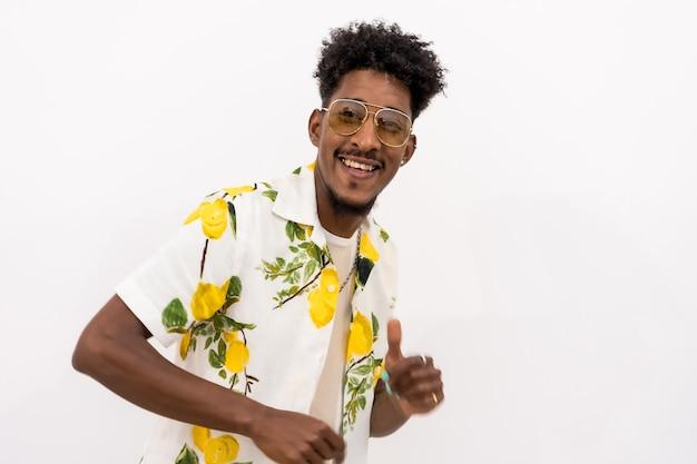 Een jonge cubaanse man met een wit en groen bloemenshirt, een bril, glimlachend en dansend op een witte achtergrond, kopieer de ruimte en plak