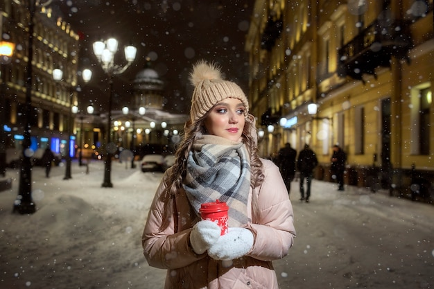 Een jonge dame in wanten en een hoed op een winternacht onder de lichten. winter portret van een mooi meisje in st. petersburg. mooie kerstnacht met een kopje koffie.