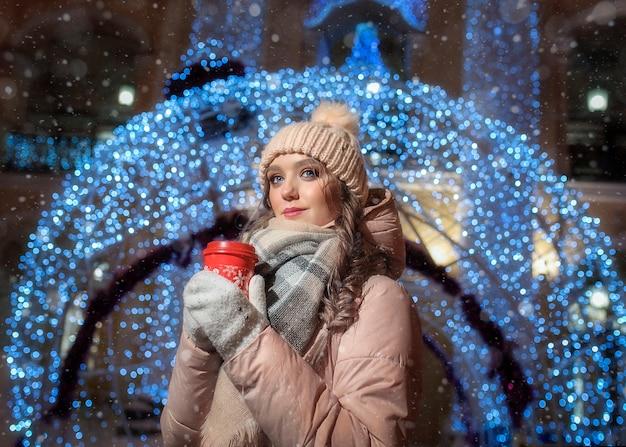 Een jonge dame op de achtergrond van een bokeh van een grote kerstbal. winter portret van een mooi meisje. portret van een meisje op een winternacht met een kopje koffie in haar handen.
