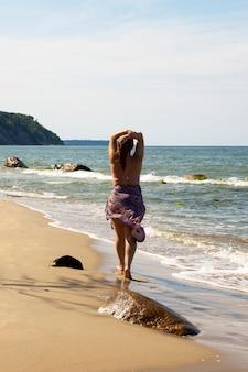 Een jonge dame staat aan zee in een pareo, met haar rug naar de camera, te zonnebaden. oostzee