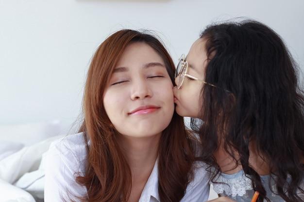 Een jonge dochter kust vrolijk de wang van haar moeder op de slaapkamer.