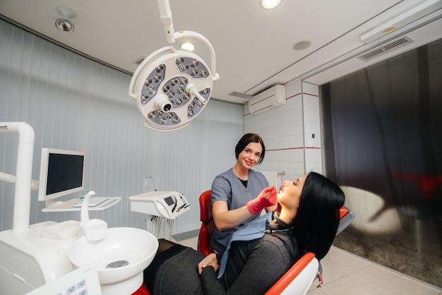 Een jonge dokter behandelt de tanden van zijn patiënt. tandheelkunde