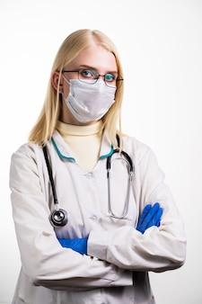 Een jonge dokter in uniform, met een beschermend masker en een bril, is boos. de dokter zweert dat mensen de voorzorgsmaatregelen niet volgen en de verspreiding van het virus voorkomen.