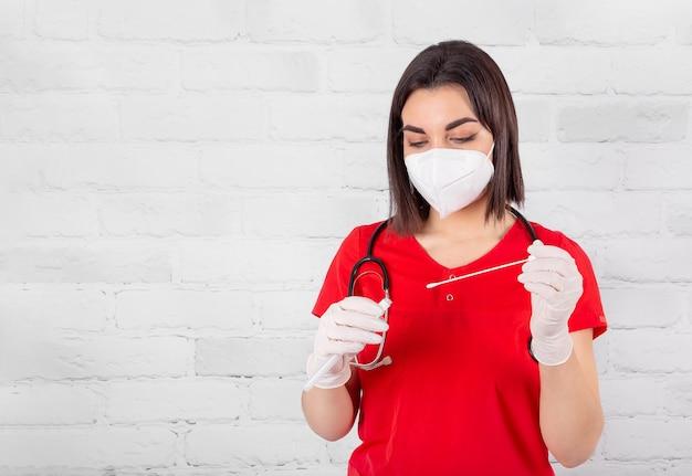 Een jonge dokter met een beschermend gezichtsmasker en handschoenen met een reageerbuis