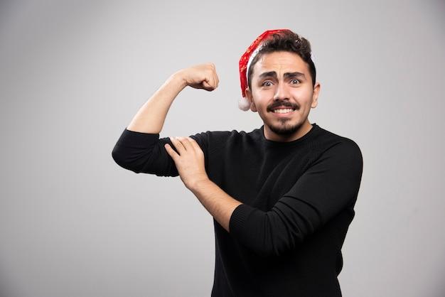 Een jonge donkerbruine man in de hoed van de kerstman toont zijn spieren en poseren