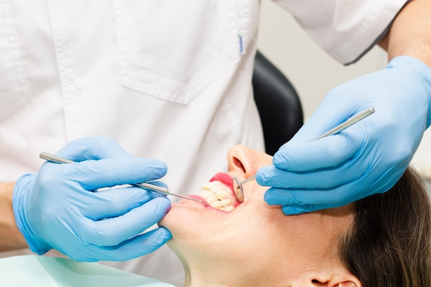 Een jonge donkerharige vrouw bezoekt de tandarts.