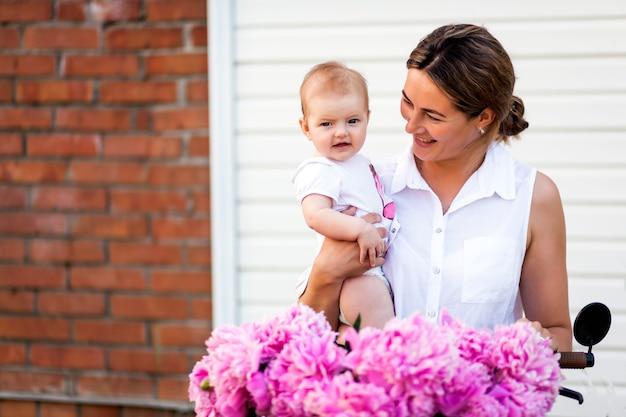 Een jonge donkerharige vrouw in een wit overhemd houdt een klein meisje in haar hand