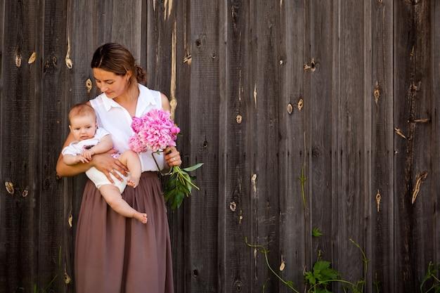 Een jonge donkerharige vrouw in een wit overhemd in een beige rok houdt een kleine baby in haar hand en een mooi boeket roze pioenrozen op de achtergrond van een houten hek