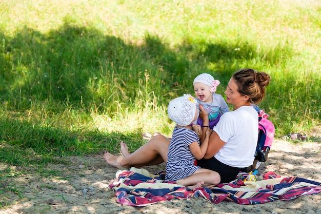 Een jonge donkerharige vrouwelijke moeder die met haar kinderen speelt: een vijfjarig meisje en een kleine baby zittend op een picknick in een groen park op een zomerdag