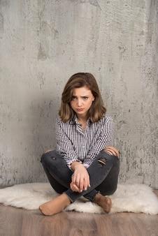 Een jonge droevige vrouw in plaidoverhemd die haar wangen blaast.