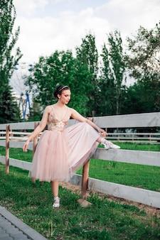 Een jonge elegante ballerina heeft haar voet opgetild op het houten bord van de omheining van de paardenstal in de...