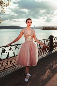 Een jonge elegante vrouwelijke ballerina in een roze jurk met een volle organza rok een ballerina poseert in de buurt van een ...