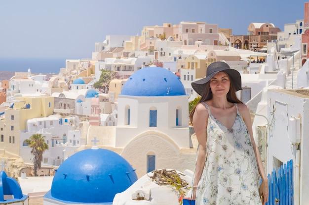 Een jonge en aantrekkelijke vrouw in een witte jurk en zwarte hoed